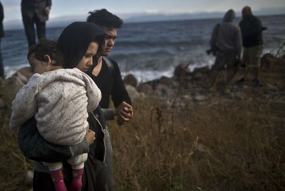 An Afghan family arrives on the Greek island of Lesbos after sailing on a dinghy from Turkey. Photo: Muhammed Muheisen, Associated Press