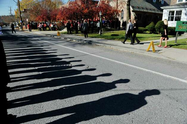 Firefighters from area fire departments cast shadows on the ground as mourners make their way into St. Patrick's Church for the funeral of  Robert Prior on Wednesday, Nov. 4, 2015, in Ravena, N.Y.  Prior was  killed when he was hit by a wrong-way driver on Saturday.  Prior was the current commissioner of the Coeymans Fire District and he was past chief of the Coeymans Fire Company.  (Paul Buckowski / Times Union) Photo: PAUL BUCKOWSKI / 00034075A