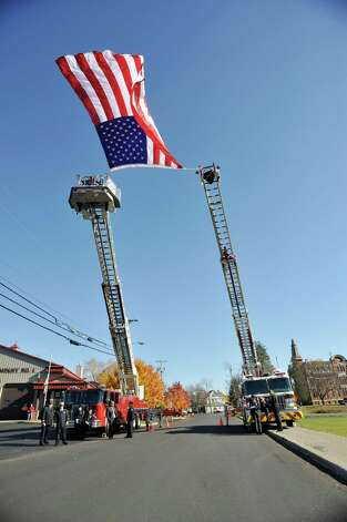 A large flag flies between two ladder trucks at the Coeymans Fire Company No. 1 for the funeral of  Robert Prior on Wednesday, Nov. 4, 2015, in Ravena, N.Y.  Prior was  killed when he was hit by a wrong-way driver on Saturday.  Prior was the current commissioner of the Coeymans Fire District and he was past chief of the Coeymans Fire Company.  (Paul Buckowski / Times Union) Photo: PAUL BUCKOWSKI / 00034075A