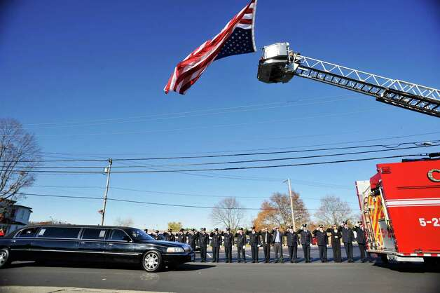 Firefighters salute as the vehicle carrying the family of Robert Prior drives by during the funeral for Prior on Wednesday, Nov. 4, 2015, in Ravena, N.Y.  Prior was  killed when he was hit by a wrong-way driver on Saturday.  Prior was the current commissioner of the Coeymans Fire District and he was past chief of the Coeymans Fire Company.  (Paul Buckowski / Times Union) Photo: PAUL BUCKOWSKI / 00034075A