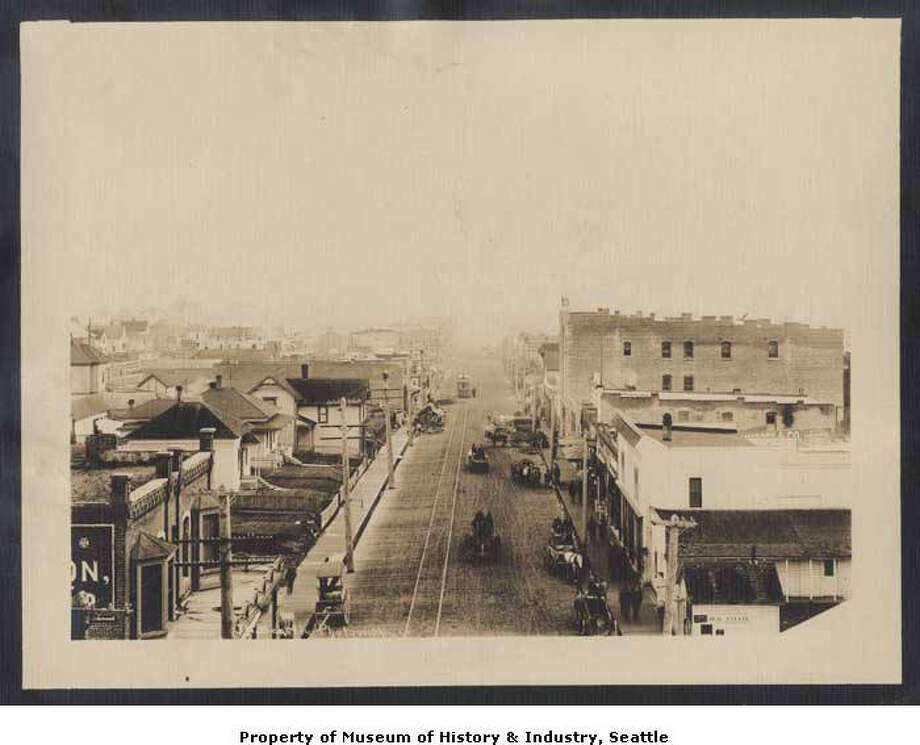 """""""In 1887, the town of Ballard was founded across Salmon Bay from Seattle. Many of its earlier residents were Scandinavian fishermen and their families. After the 1889 fire destroyed Seattle's business district, including Yesler's Mill, the lumber industry moved to Ballard. By 1904, the town had 10,000 residents. Most of the men either fished or worked at the lumber and shingle mills. Ballard became a part of Seattle in 1907 . This early 1900s photo shows a view along Ballard Avenue, looking southeast. Horsedrawn wagons wait by the wooden sidewalks, and an electric streetcar runs on its tracks in the distance."""" -MOHAI. Photo courtesy MOHAI, Seattle Photographic Company Collection, image number shs14001. Photo: Courtesy MOHAI"""