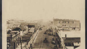 """""""In 1887, the town of Ballard was founded across Salmon Bay from Seattle. Many of its earlier residents were Scandinavian fishermen and their families. After the 1889 fire destroyed Seattle's business district, including Yesler's Mill, the lumber industry moved to Ballard. By 1904, the town had 10,000 residents. Most of the men either fished or worked at the lumber and shingle mills. Ballard became a part of Seattle in 1907 . This early 1900s photo shows a view along Ballard Avenue, looking southeast. Horsedrawn wagons wait by the wooden sidewalks, and an electric streetcar runs on its tracks in the distance."""" -MOHAI. Photo courtesy MOHAI, Seattle Photographic Company Collection, image number shs14001."""