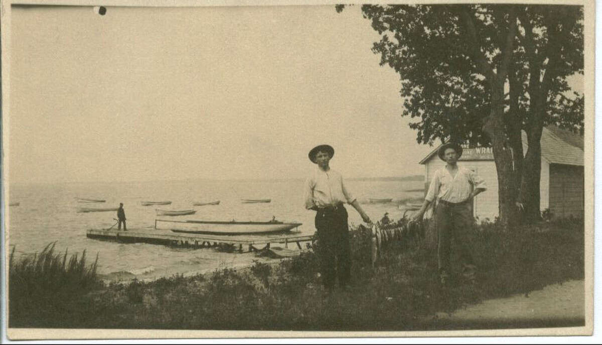 This photo of two men holding a string of fish between them is dated to July 27, 1906. It appears to be on the west shore of Ballard. Photo courtesy Nordic Heritage Museum.