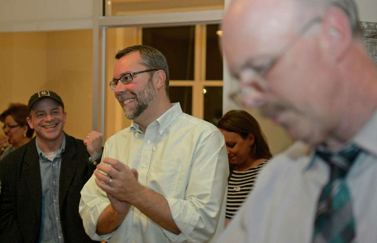 Democratic candidate for mayor in New Milford, David Gronbach applauds as his campaign manager Peter Mullen, right, reads off results from one of the districts on election night. Gronbach waited for the election results in his New Milford office.