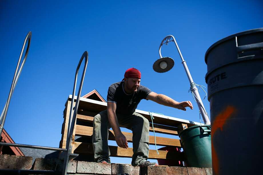 A fisherman reaches for a trash bin, while doing daily chores on the Willanina crab and fishing boat, at Fisherman's Wharf in San Francisco, California on Wednesday, November 4, 2015. Despite state health officials concerns that crabs along the coast of California are too toxic to eat, fisherman continue to go about their chores to get ready for the season. Photo: Gabrielle Lurie, Special To The Chronicle