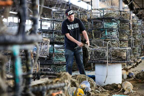 San Francisco based fisherman, Kegan Foster cleans crab traps at a garage in Fisherman's Wharf in order to get ready for the upcoming season, in San Francisco, California on Wednesday, November 4, 2015. Fisherman continue to get themselves ready for the season despite state health officials concerns that crabs along the coast of California are too toxic to eat.