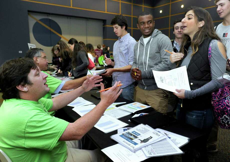 John Kmetz, left, with the Community Credit Union of New Milford, haggles with Natalie Truglia, 17, right, of Stamford, over the price of a car. The two are participating in a financial-reality fair organized by area credit unions for high school students. The event was held Wednesday at the Western Connecticut State University's west side campus. Photo: Carol Kaliff / Hearst Connecticut Media / The News-Times