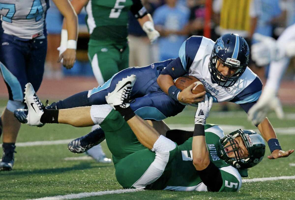 Johnson quarterback Josh Theissen is upended by Reagan's Leyton Leone in the fist quarter at Comalander Stadium on Oct. 3, 2015.