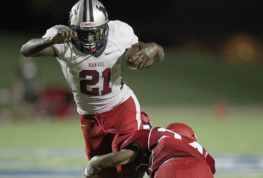 Running back D'Vaughn Pennamon (21) of the Manvel Mavericks is tackled by defensive back Zafir Murphy (24) of the North Shore Mustangs in the second half on Friday, September 4, 2015 at Galena Park ISD Stadium in Houston, TX.(For the Chronicle / Thomas B. Shea) Photo: Thomas B. Shea / © 2015 Thomas B. Shea