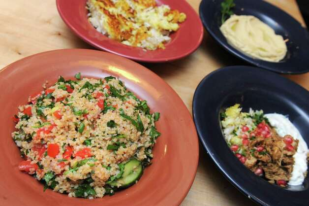 From front clockwise, tabouli salad, tah dig, hummus and walnut pomegranate chicken with yogurt on Tuesday Oct. 27, 2015 in Delmar, N.Y. (Michael P. Farrell/Times Union) Photo: Michael P. Farrell / 10033816A