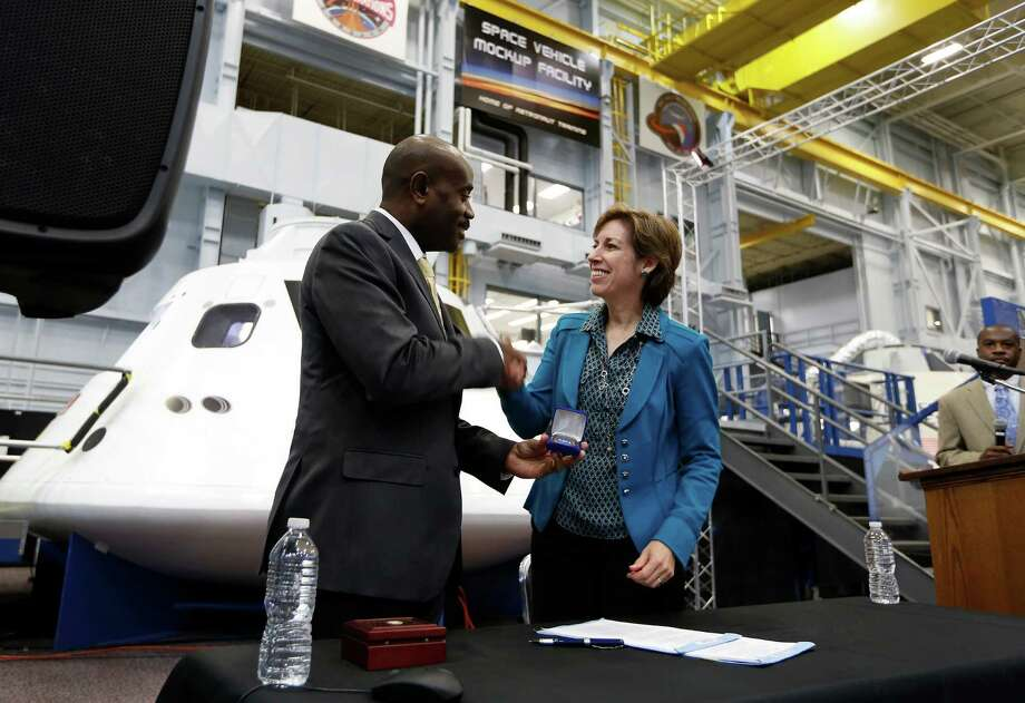 Lance Lyttle of the Houston Airport System and Ellen Ochoa of the Johnson Space Center shake on the agreement. Photo: Steve Gonzales, Staff / © 2015 Houston Chronicle