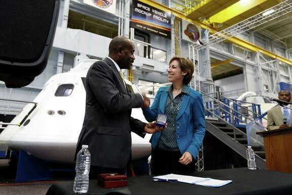 Lance Lyttle of the Houston Airport System and Ellen Ochoa of the Johnson Space Center shake on the agreement.