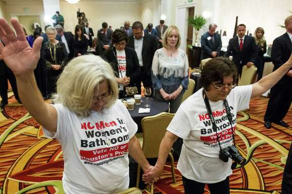 Rita Palomarez, left, and Linda Rodriguez pray at an election-watch party attended by opponents of the Houston Equal Rights Ordinance.