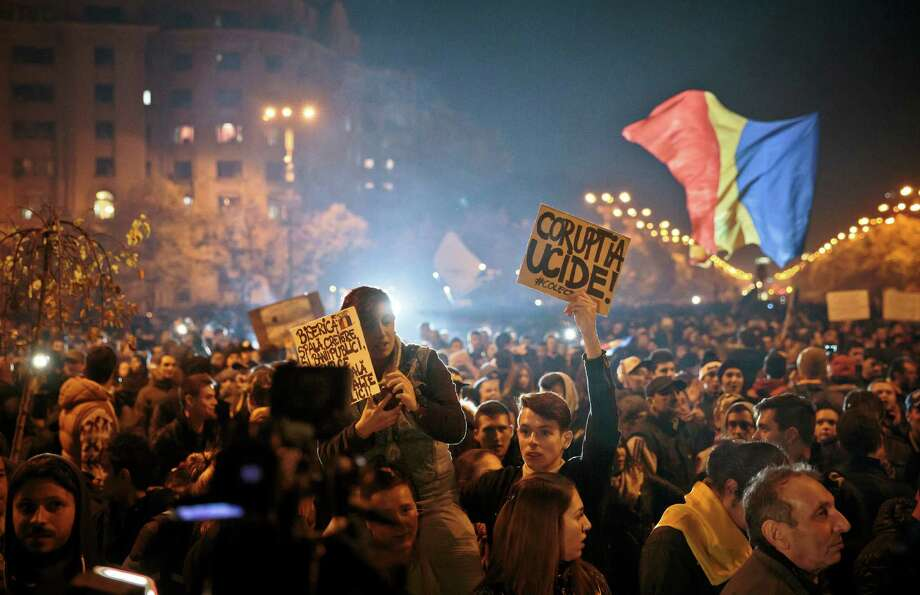 "Protesters hold banners reading ""Corruption kills"" and ""The Church washes brains and launders public money"" during a rally Wednesday joined by thirty-five thousand people in Bucharest, Romania.  Photo: Vadim Ghirda, STF / AP"