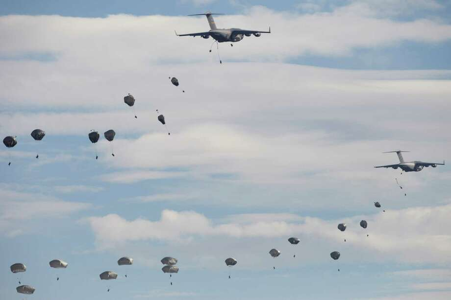US paratroopers from the 82nd Airborne Division from Fort Bragg in North Carolina, jump of the US C-17 Globemaster aircraft during a NATO military demonstration in Zaragoza, Spain, Wednesday Nov. 4, 2015. NATO is putting on its most fearsome display of military might in over a decade with soldiers, ships and planes meant to hone and test its abilities as well as send an unequivocal sign to Russia and other real or potential foes. For three weeks which started Oct. 21, more than 36,000 personnel from all 28 NATO allies and eight partner nations, 160 aircraft and 60 ships will be taking part in exercises across a wide swath of southern Europe from Portugal to Italy. (AP Photo/Abraham Caro Marin) Photo: Abraham Caro Marin, STR / AP