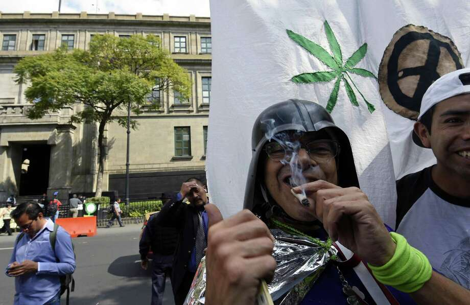 Protestors in a low-key demonstration Wednesday in front of the Supreme Court of Justice in Mexico City support the legalization of marijuana. The Supreme Court began discussing the possibility of depenalizing marijuana for recreational use.  Photo: ALFREDO ESTRELLA, Staff / AFP