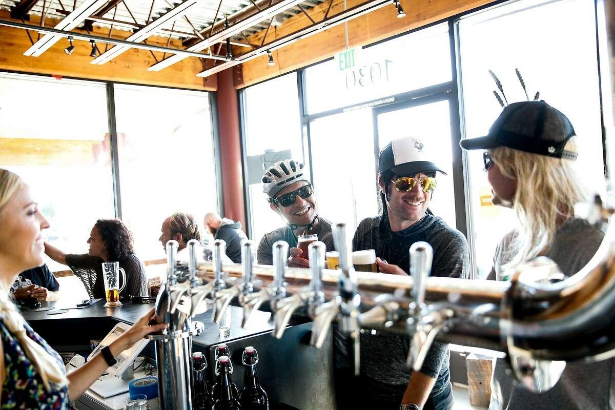 Johnny Machado, (left) of Bakersfield, Mark Vanover of Capitola and Sascha Steen of Santa Clara drink beer at New Bohemia, Santa Cruz's newest brewery.