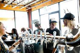 Johnny Machado, left, of Bakersfield, Mark Vanover, center, of Capitola, and Sascha Steen, right, of Santa Clara, order beers at New Bohemia Brewing Company in Santa Cruz, Calif., on Sunday, November 1, 2015.