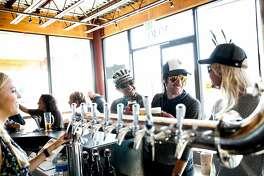 Johnny Machado, left, of Bakersfield, Mark Vanover, center, of Capitola, and Sascha Steen, right, of Santa Clara, order beers at New Bohemia Brewing Company in Santa Cruz, Calif., on Sunday, November 1, 2015.