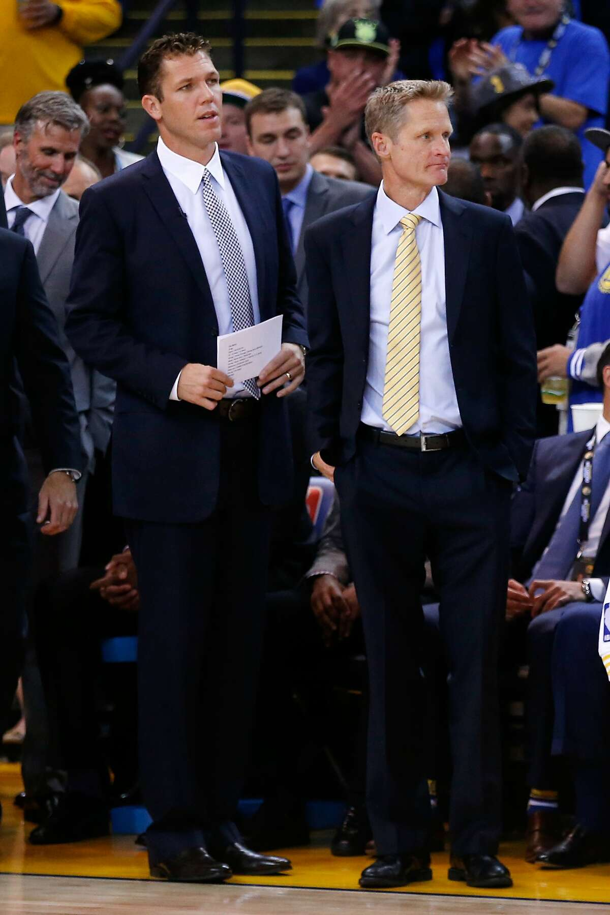 (Left to right) Interim head coach Luke Walton and head coach Steve Kerr of the Golden State Warriors stand by the bench prior to the NBA season opener at ORACLE Arena on October 27, 2015 in Oakland, California.