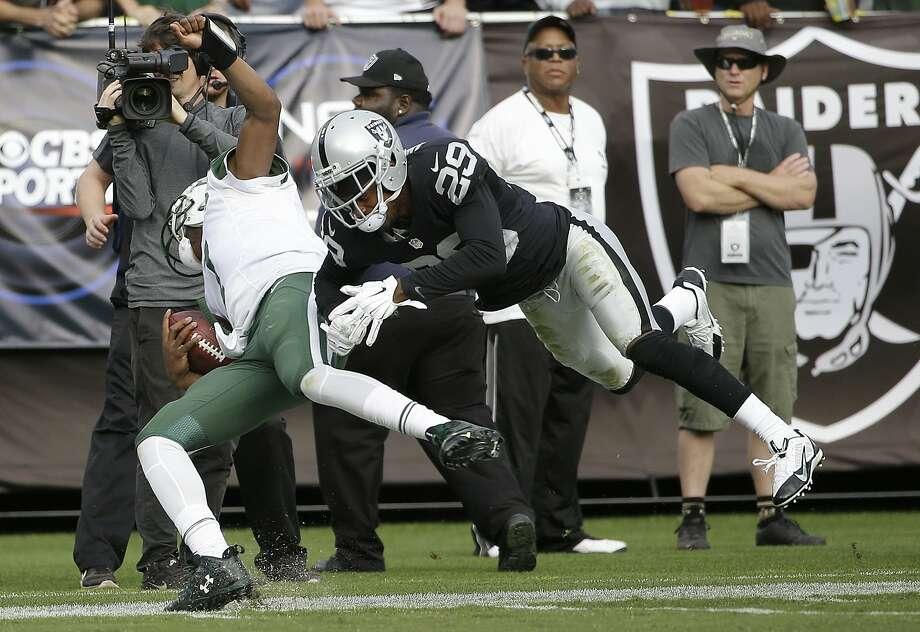 Jets quarterback Geno Smith takes a big second-half hit deliv ered by tough-minded Raiders cornerback David Amerson. Photo: Marcio Jose Sanchez, Associated Press