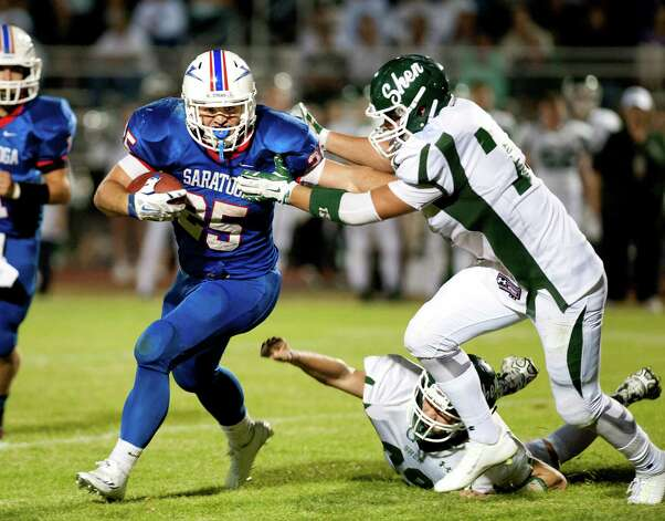 Saratoga's Dakota Harvey, center, stiff arms Shenendehowa's Tyler Comito, right, to set up a touchdown during their football game on Friday, Sept. 25, 2015, at Saratoga Springs High in Saratoga Springs, N.Y. (Cindy Schultz / Times Union) Photo: Cindy Schultz / 10033490A