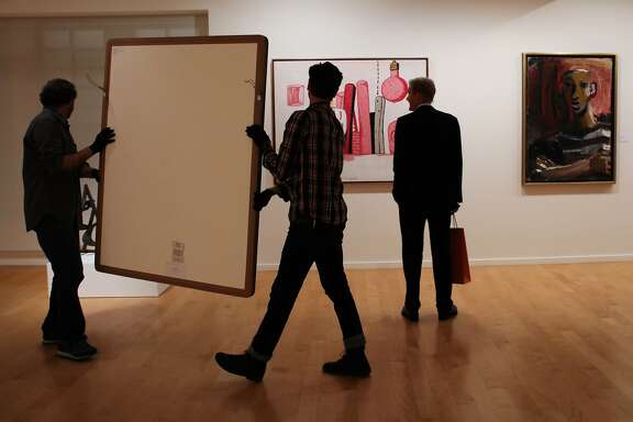 Scott Schryver (left) and Naaman Rosen (center) carry a painting through the John Berggruen Gallery, as Edward Sickel (right) looks on, in San Francisco, California on Tuesday, November 3, 2015.