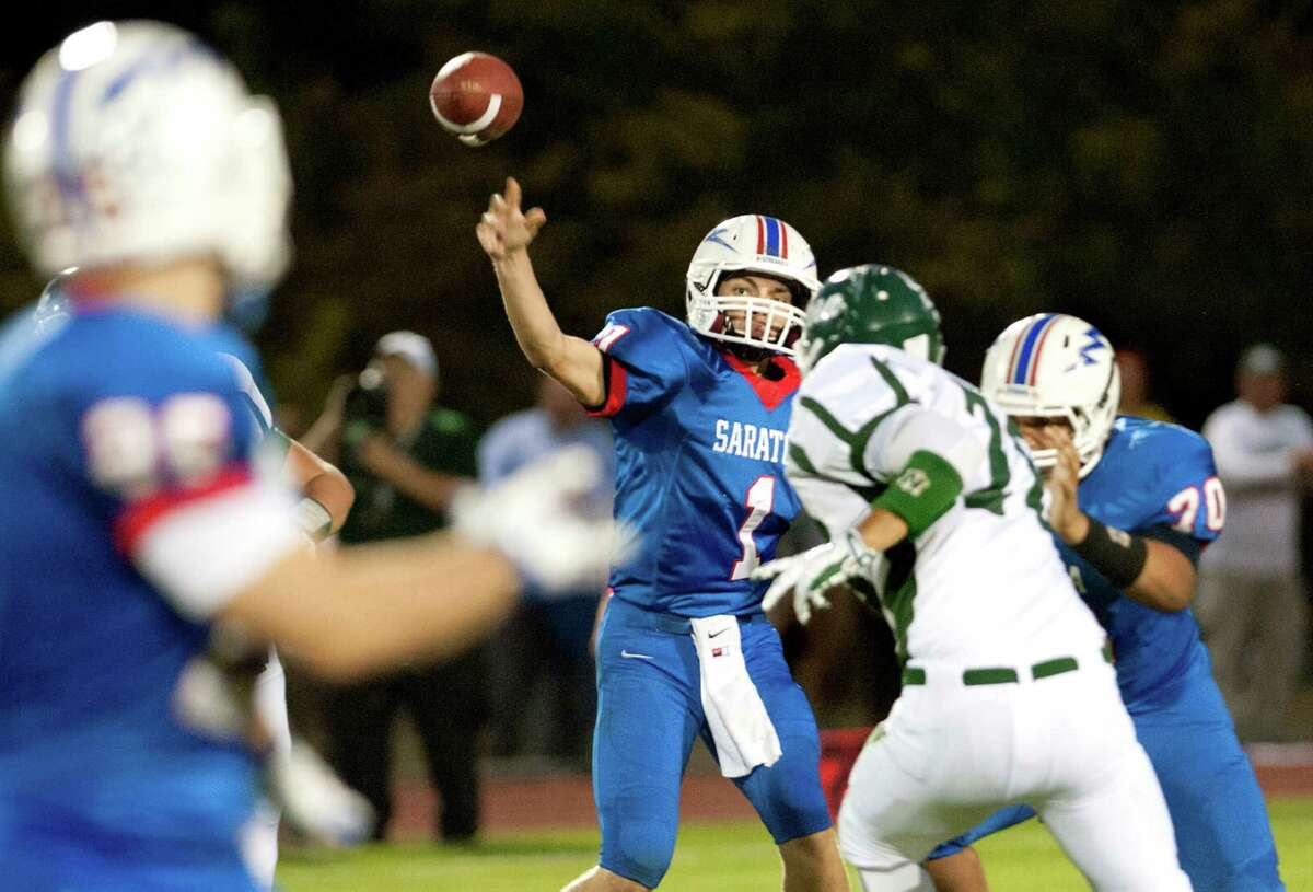Saratoga's quarterback Brian Williams, center, throws a pass to Dakota Harvey, left, during a game against Shenendehowa on Friday, Sept. 25, 2015.