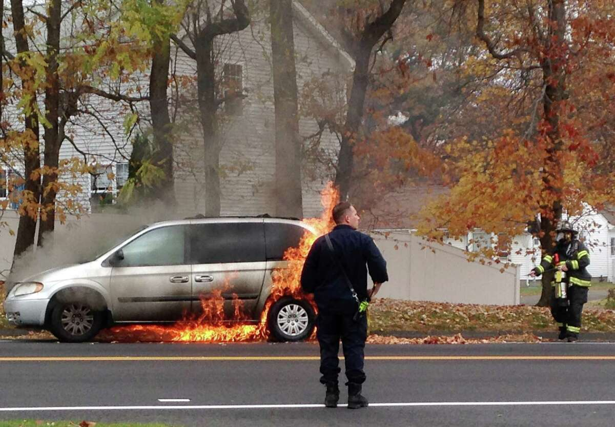 Firefighters and police responded to a car fire on Tunxis Hill Cut Off in Fairfield, Conn. on Thursday Nov. 5, 2015. Flames from the silver mini-van ignited roadside leaves. No one was inside the vehicle and police were looking for the owner.