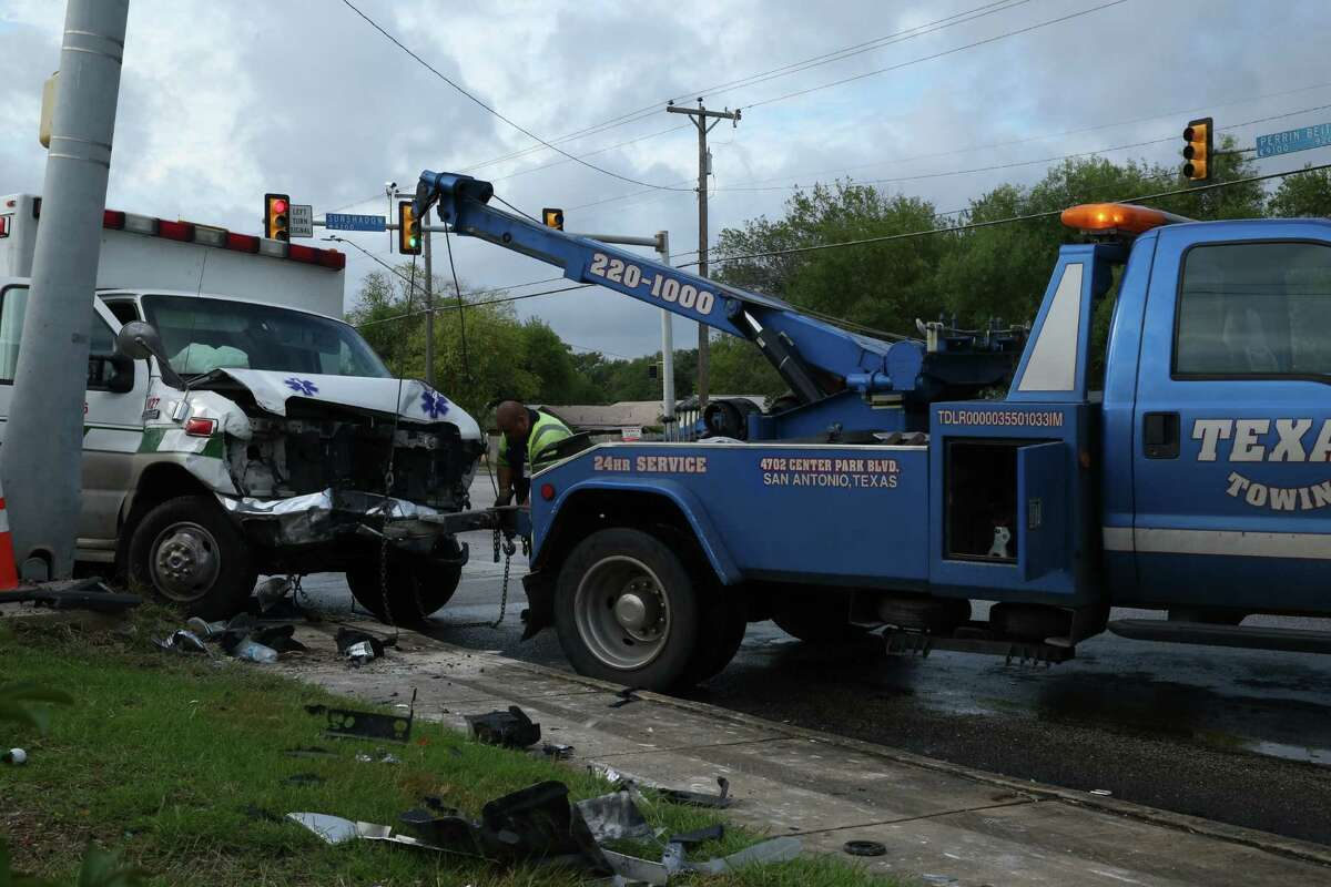 A Texas Towing driver prepares to move an ambulance after the vehicle crashed into a traffic light pole today at the corner of Perrin Beitel and Sunshadow in San Antonio.