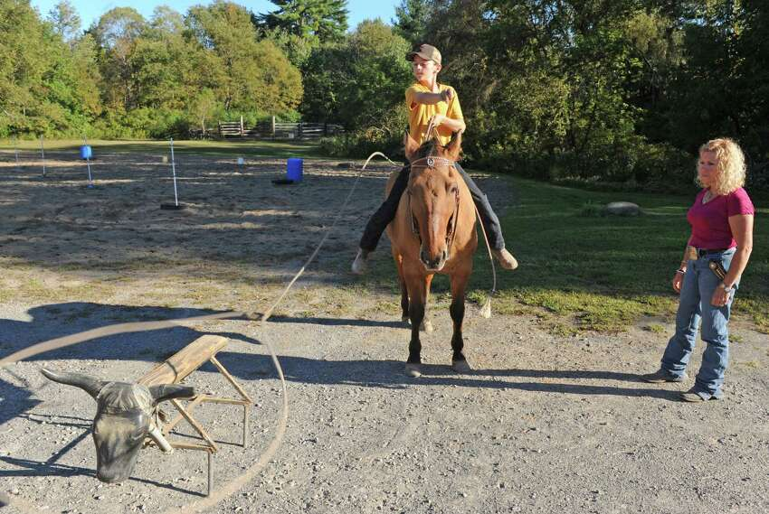 Rodeo coach Jennifer Romriell, right, works with student 14-year-old Evan Meashaw on his steer roping Wednesday Sept. 23, 2015 in Broadalbin, N.Y. (Michael P. Farrell/Times Union)