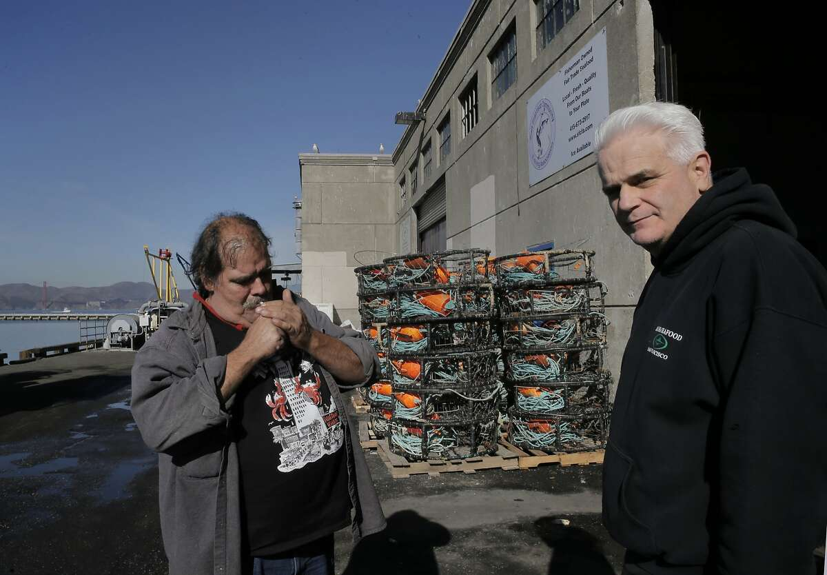 Larry Collins, (left) the president of the San Francisco Community Fishing Association, with local fish buyer Jude Smithson of Aloha Seafood, near crab pots on Pier 45 in San Francisco, Calif. on Thurs. November 5, 2015.