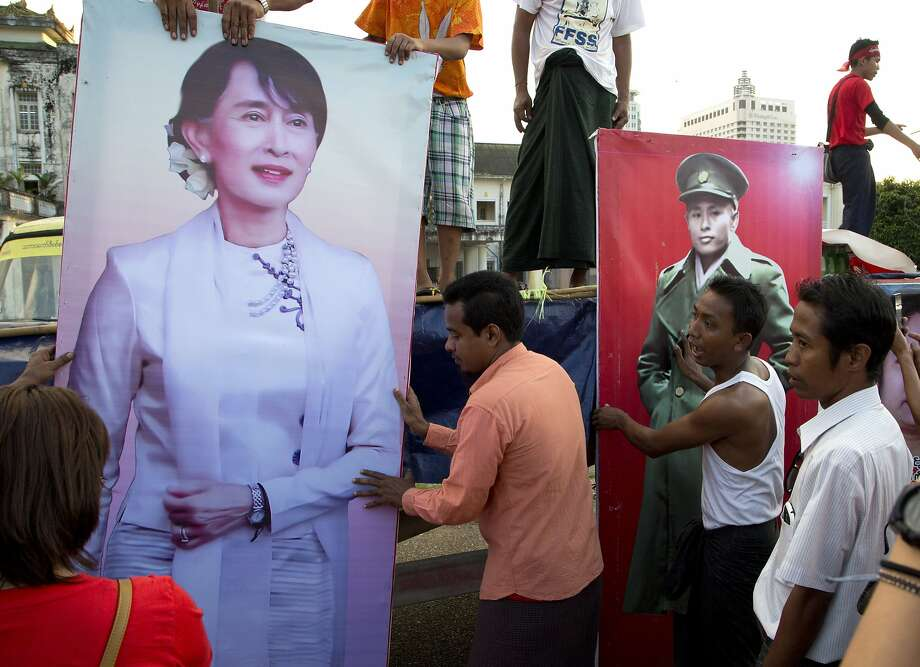 Supporters of Aung San Suu Kyi place posters of her and her late father, Aung San, on the final day of campaigning in Rangoon. Photo: Mark Baker, Associated Press