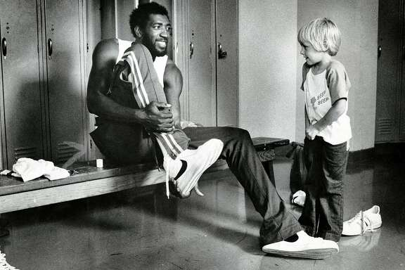 Golden State Warriors forward Clifford Ray talks to Rick Barry's son Brent in the locker room. Sept. 21, 1976.