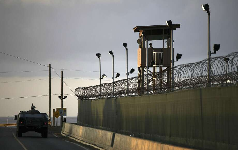 A U.S. trooper stands in the turret of a vehicle with a machine gun (left) as a guard looks out from a tower at the detention facility of Guantanamo Bay U.S. Naval Base in Cuba. Photo: Brennan Linsley, Associated Press