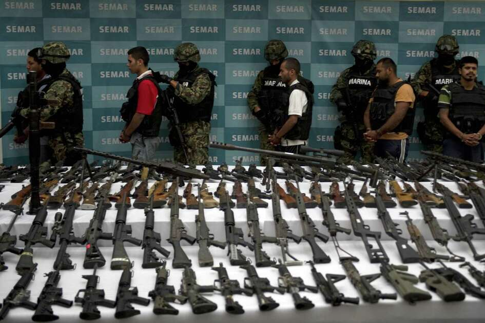 Mexican marines escort five alleged drug traffickers of the Zetas drug cartel in front of hand grenades, firearms, cocaine and military uniforms seized to alleged members of the Zetas drug traffickers cartel and presented to press on June 9, 2011 at the Navy Secretaryship in Mexico City. Fiven men were arrested and more than two hundred rifles, eleven pistols, military uniforms, differents caliber ammunitions and more than 200 kg of cocaine were seized in the Coahuila and Nuevo Leon States by the Navy. AFP PHOTO/ Yuri CORTEZ