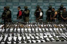 FILE -- Mexican marines escort five alleged drug traffickers of the Zetas drug cartel in front of hand grenades, firearms, cocaine and military uniforms seized to alleged members of the Zetas drug traffickers cartel and presented to press on June 9, 2011 at the Navy Secretaryship in Mexico City.