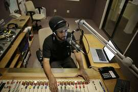 """DJ Adam Tadesse works in the control room during his show """"Wake the Town"""" at KPOO  on Wednesday, November 4,  2015 in San Francisco, Calif."""