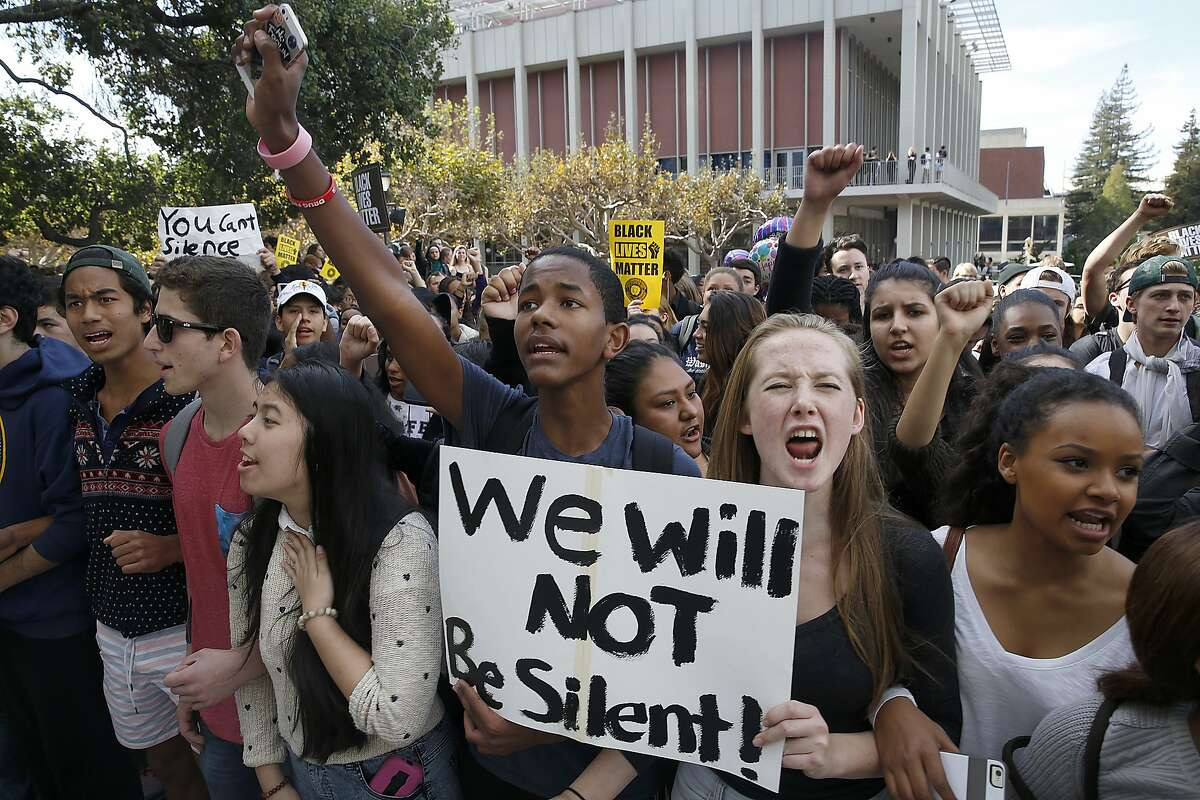 Berkeley High School students including Nancy Nguyen (left), Berenabas Lukas (middle) and Simone Ewell Szabo (right) stage a walkout demonstration at Sproul plaza over a racist post on the school website in Berkeley, Calif., on Thursday, November 5, 2015.