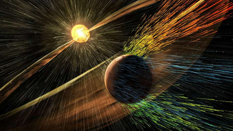 This image made available by NASA on Thursday, Nov. 5, 2015 shows an artist's rendering of a solar storm hitting the planet Mars and stripping ions from the planet's upper atmosphere. NASA's Mars-orbiting Maven spacecraft has discovered that the sun robbed the red planet of its once-thick atmosphere and water. On Thursday, scientists reported that even today, the solar wind is stripping away about 100 grams of atmospheric gas every second. (Goddard Space Flight Center/NASA via AP) Photo: Associated Press