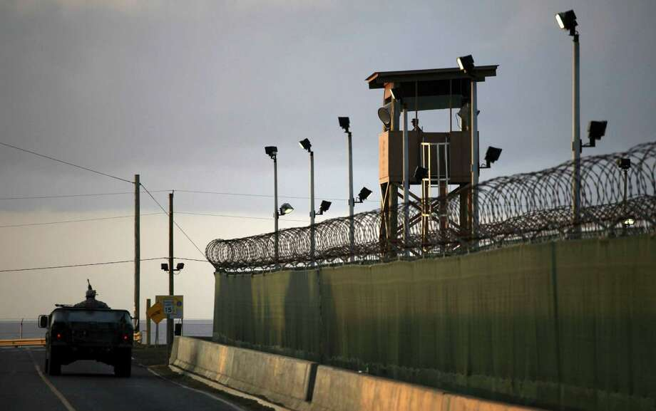 FILE – In this March 30, 2010 file photo, reviewed by the U.S. military, a U.S. trooper stands in the turret of a vehicle with a machine gun, left, as a guard looks out from a tower at the detention facility of Guantanamo Bay U.S. Naval Base in Cuba. The House on Thursday overwhelmingly passed a revised $607 billion defense policy bill that restricts President Barack Obama's efforts to close the military prison at Guantanamo Bay, Cuba.  (AP Photo/Brennan Linsley, File) Photo: Brennan Linsley, STF / AP