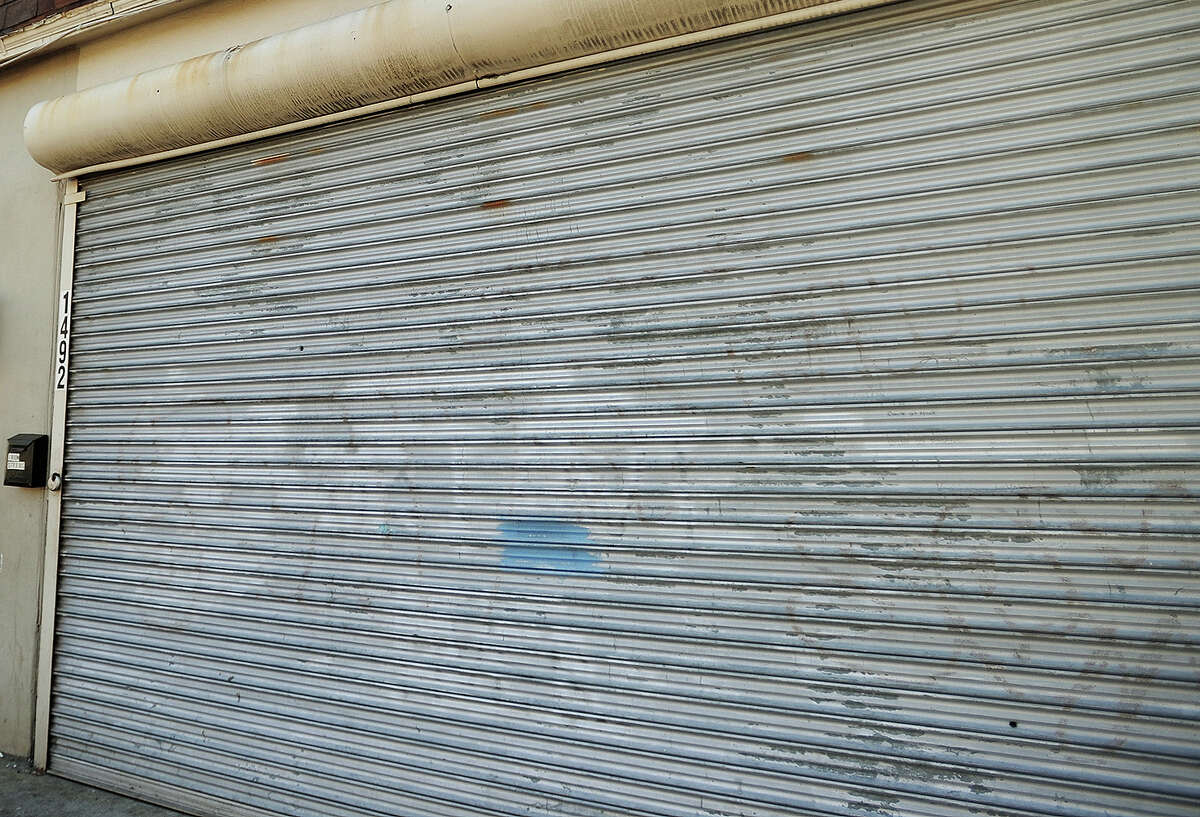 Bullet holes can be seen in the corrugated metal storefront from Sunday's shooting outside 1492 Stratford Avenue in Bridgeport, Conn. on Tuesday, October 27, 2015. The neighborhood has been the scene of ongoing gang related shooting incidents in recent weeks.