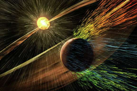 An artist's rendering shows a solar storm hitting Mars and stripping ions from the planet's upper atmosphere. NASA's Mars-orbiting MAVEN craft has discovered that solar storms rob the red planet of about 10 pounds of atmosphere per second.