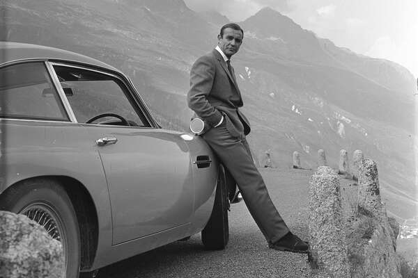 "Sean Connery as James Bond with his well-equipped Aston Martin in ""Goldfinger."""