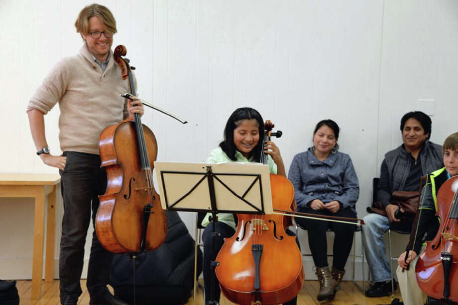 Haven String Quartet cellist Philip Boulanger instructs a Tuning In to Music student during a class at the Greenwich Arts Council building Photo: Contributed / Contributed Photo / Greenwich Time Contributed