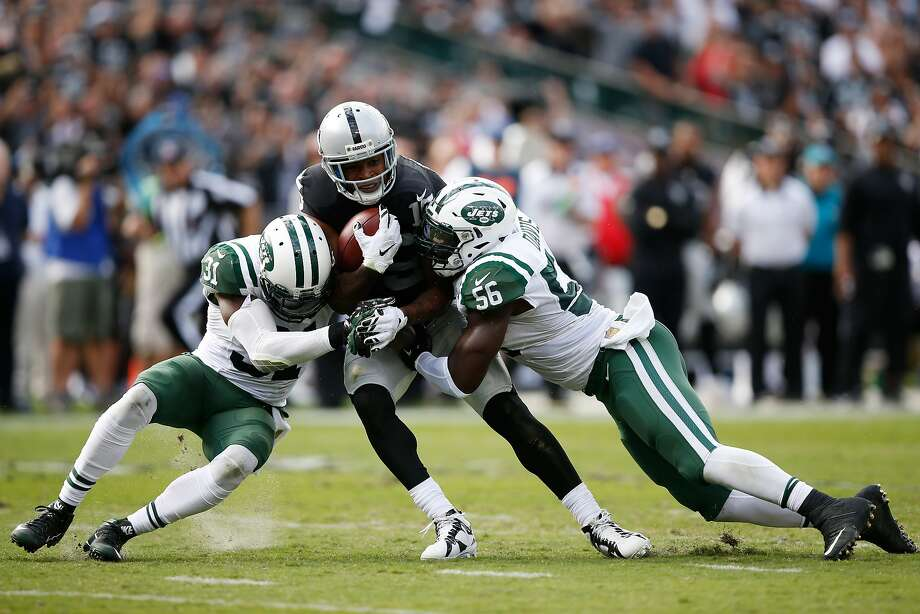 Michael Crabtree #15 of the Oakland Raiders breaks a tackle from Demario Davis #56 and Antonio Cromartie #31 of the New York Jets as he runs for a 36-yard touchdown reception against the New York Jets during their NFL game at O.co Coliseum on November 1, 2015 in Oakland. Photo: Ezra Shaw, Getty Images