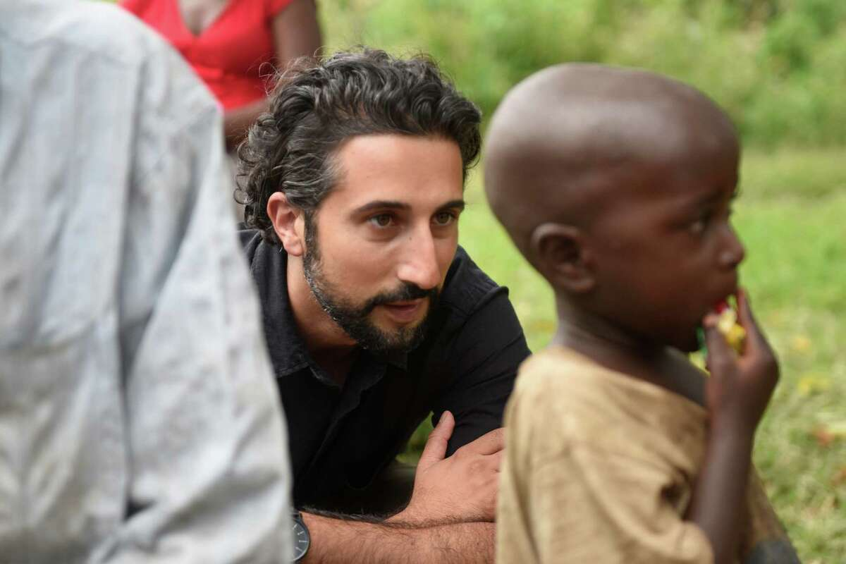 Dr. Sohi Ashraf, of Norwalk, Conn., looks ahead at an HIV positive patient's child during an ACCESS Health Training Institute home visit in the rural town of Nakaseke, Uganda.