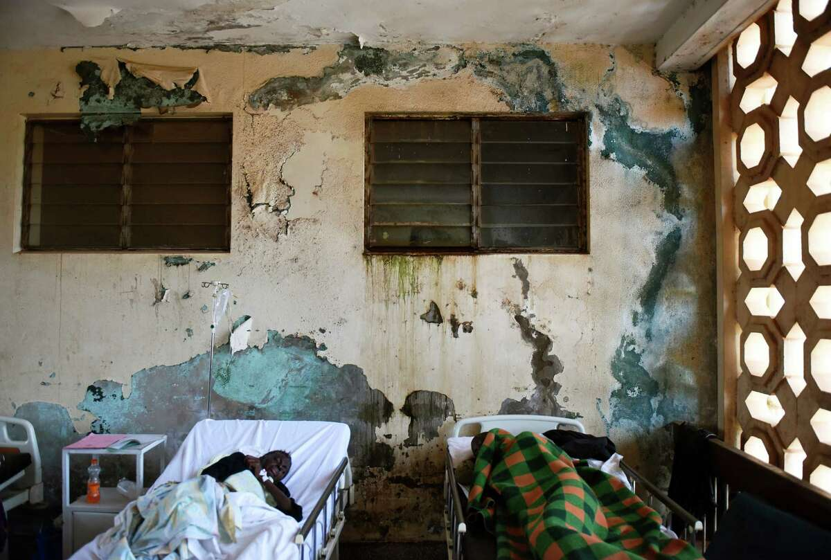 Patients lie in their beds against a wall of peeling paint in the infectious disease ward at Mulago Hospital in the capital city of Kampala, Uganda.