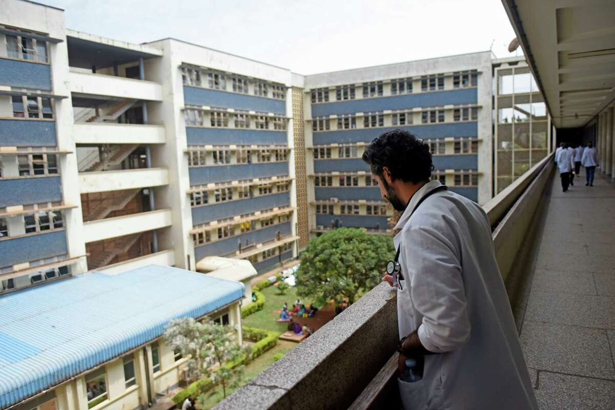 Dr. Sohi Ashraf, of Norwalk, Conn., looks down upon the courtyard at Mulago Hospital in the capital city of Kampala, Uganda. Friends and family of patients must be present at the hospital to tend to their loved ones who are unable to get food or bathe themselves. Food, hygiene services and even blankets are not provided to patients at the hospital.