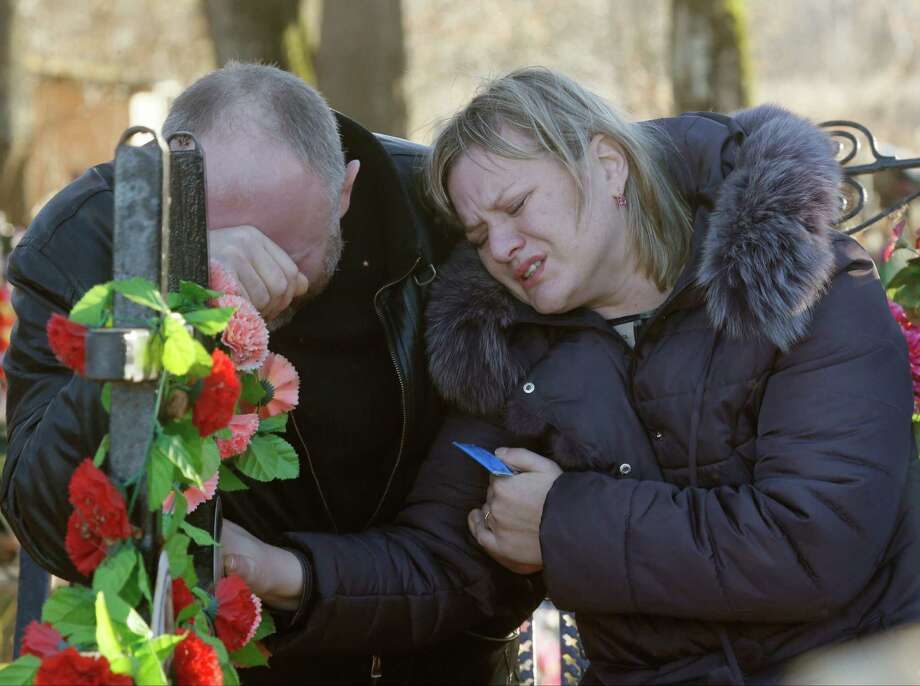 Plane crash victim Nina Lushchenko's nephew Pavel and daughter Veronika stand at her grave after her funeral at a cemetery Thursday in Sitnya, Russia. Photo: Dmitry Lovetsky, STF / AP